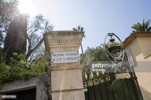 A plaque reading 'Old Residence of King Leopold II' sits beside black and gold painted iron gates at the entrance to the Villa Les Cedres a...