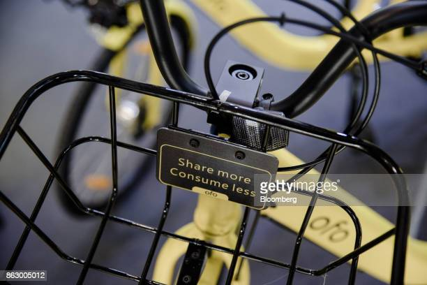 A plaque reading 'share more consume less' sits on the basket of a Ofo Inc hire bicycle during a presentation at the Autonomy urban mobility summit...