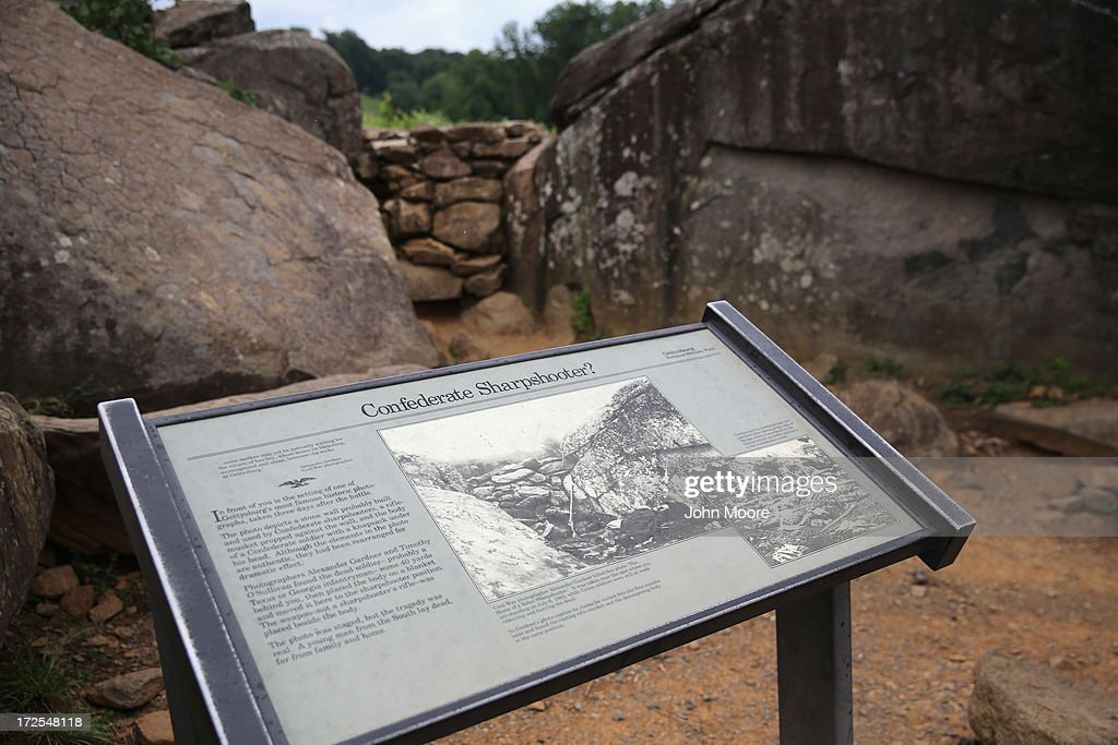 A plaque tells the story of 'The Home of a Rebel Sharpshooter' photograph at Devil's Den on July 2, 2013 in Gettysburg, Pennsylvania, the 150th anniversary of the Battle of Gettysburg. Many tourists visiting the site pose for photos there as part of their battlefield experience. The original historic image was taken there by Alexander Gardner on July 5, 1863 and featured a dead Confederate soldier with a rifle proped next to him. The photograph was later discovered to be staged, the dead body of the 'sharpshooter' having been brought from another place on the battlefield for the photograph and the gun not a sharps rifle.