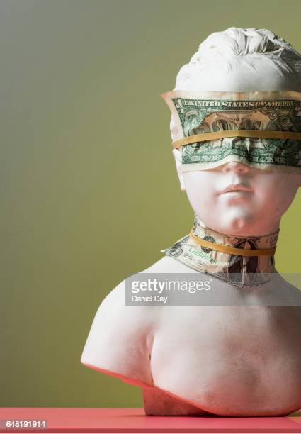 A plaster cast of a young girl with money over her eyes