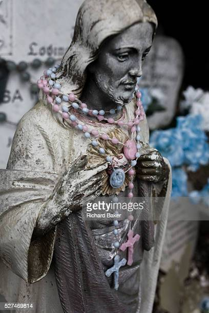A plaster figure of Jesus draped with plastic beads and a crucifix at a gravestone in a south London cemetery Seen in close detail we see the plastic...