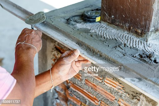 plasterer concrete worker at wall of house construction : Stock Photo