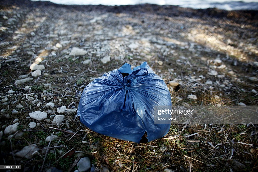 A plastic bag containing wet blankets and the clothes of immigrants who landed the previous night sits abandoned on a beach near Mytilene, on the island of Lesbos, Greece, on Saturday, Dec. 8, 2012. In recent months, Lesbos has become a hot spot for migrants as Greece struggles to cope with waves of refugees from Middle Eastern conflict even as it reels from economic crisis at home. Photographer: Kostas Tsironis/Bloomberg via Getty Images