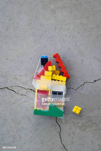Plastic block house taped together on concrete