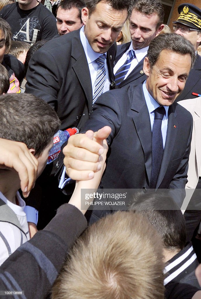 A plastic bottle is thrown by a schoolboy at France's President Nicolas Sarkozy during a visit at Charles Fauqueux college to discuss violence in French schools, on May 25, 2010 in Beauvais, northern France. A bodyguard came between Sarkozy and the water bottle which was thrown as pupils crowded around the president, some of them seeking to shake his hand.