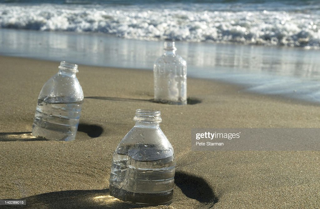 Plastic bottles buried in sand along beach front. : Stock Photo