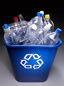Plastic bottles in trash bin with recycle sign, elevated view