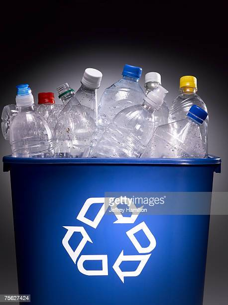 Plastic bottles in trash bin with recycle sign