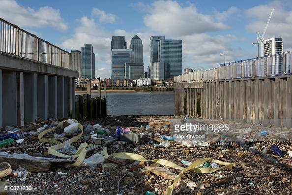 Plastic brought along by exceptionally high tides litters the high water line in front of the Canary Wharf business financial and shopping district...