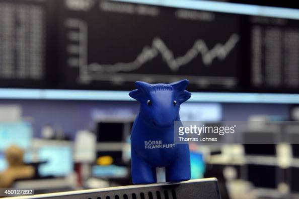 A plastic bull stands on a monitor in front of the index board that shows the DAX has broken the 10000 mark for the first time ever at the Deutsche...