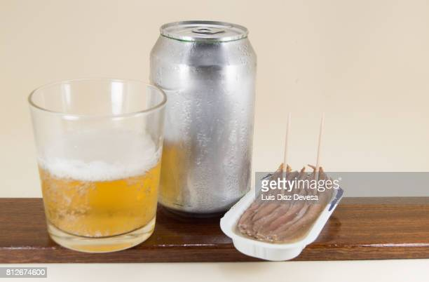 plastic can of  anchovies, beer Can and glass of beer