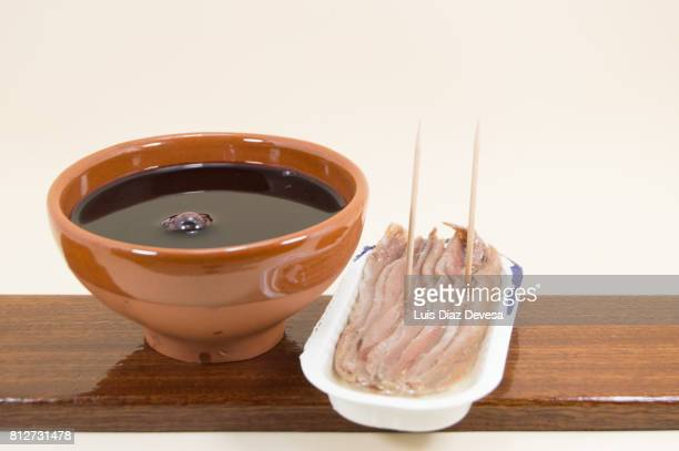 plastic can of  anchovies  in olive oil and an earthenware cup of red wine