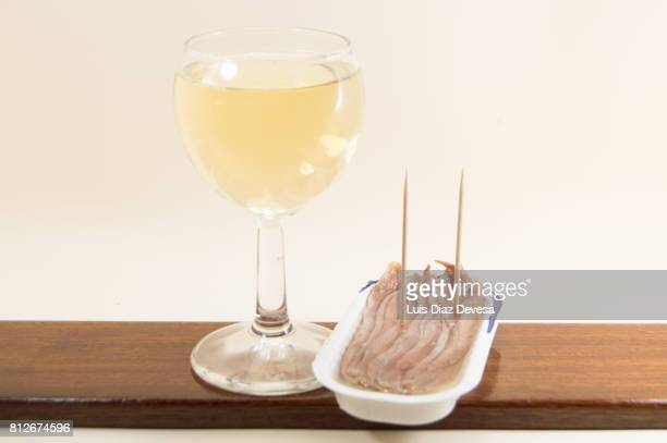 plastic can of  anchovies  in olive oil and cup white wine