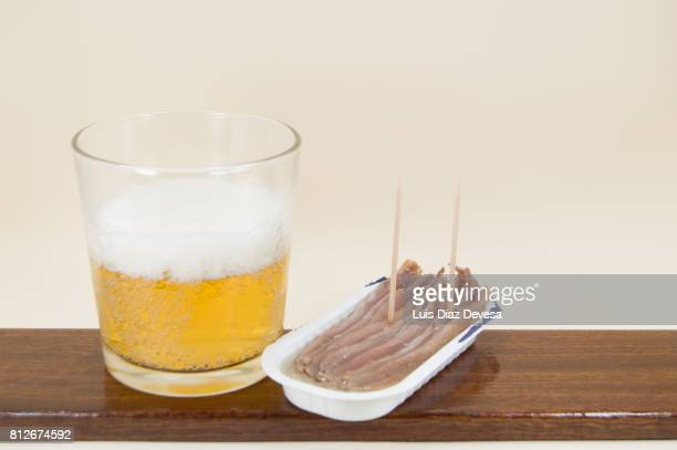 plastic can of  anchovies in olive oil and glass of beer