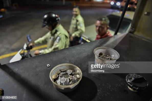 Plastic cups filled with Venezuelan bolivar coins sit on a gasoline pump as a customer waits to fuel a motorcycle in Caracas Venezuela on Wednesday...