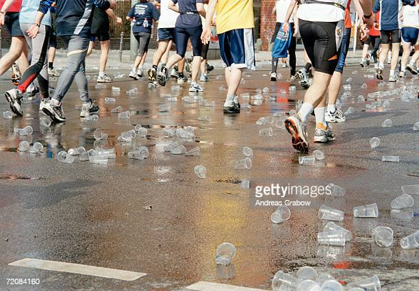 Plastic cups scattered over road beneath marathon runners