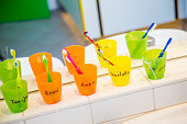 Plastic cups with toothbrushes with manes of kids in nursery
