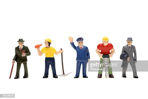 Plastic figurines of all walks of life including preacher, miner, policeman, construction worker, and businessman