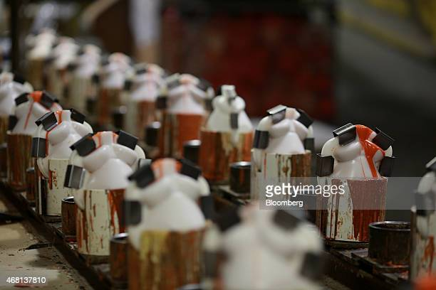 Plastic molds containing asymmetric bowling ball cores move down a conveyor belt on the assembly line at the Ebonite International manufacturing...