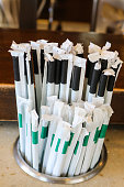 Plastic straws with paper wrappers in counter holder - the straws that many states and countries are outlawing but are still used many places