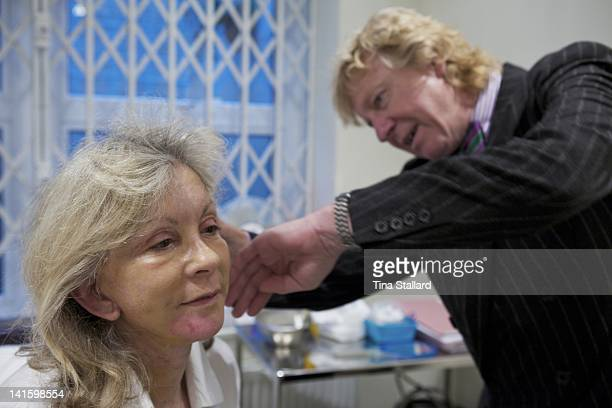 Plastic surgeon Barry Jones examines the scars behind a patient's ears a week after he carried out her facelift and surgery to reduce the prominence...