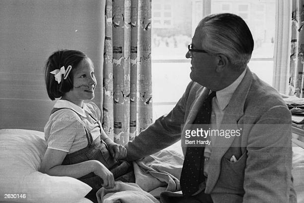 Plastic Surgeon Sir Archibald McIndoe CBE chats to a young patient at the Queen Victoria Hospital in East Grinstead Sussex where he has set up a...