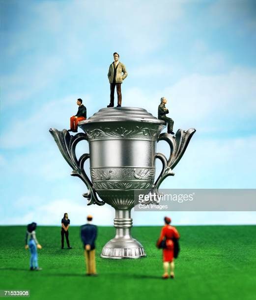 Plastic Toy People by a Large Trophy