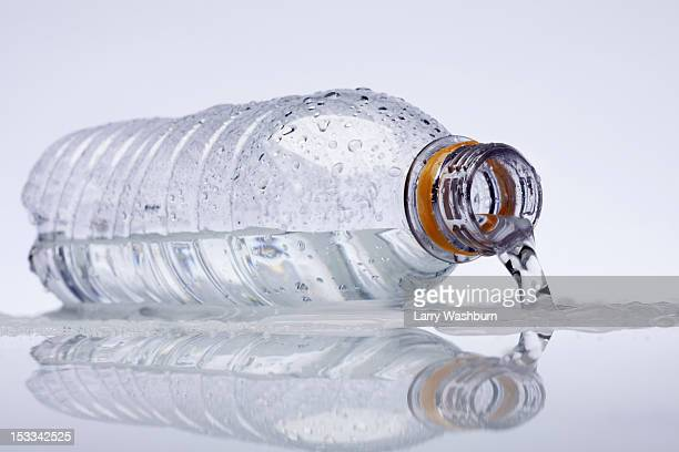 A plastic water bottle lying on its side, water spilling out