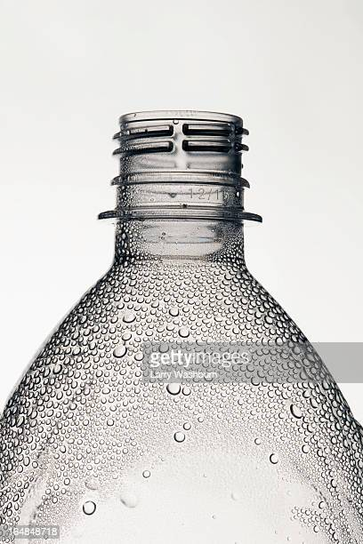A plastic water bottle without a cap that has condensation on it