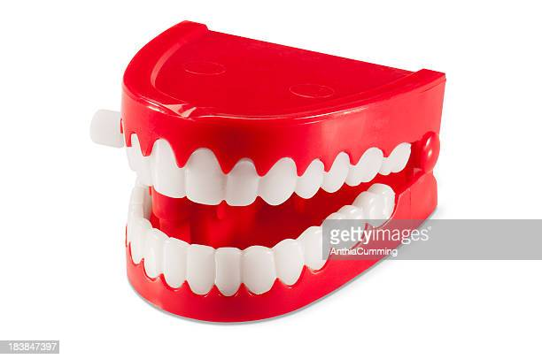 Plastic wind-up chattering joke teeth on white background