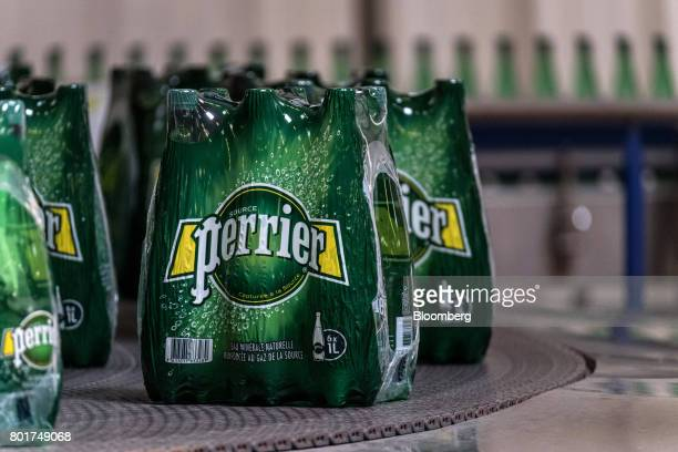 Plastic wrapped packets of Perrier mineral water bottles pass along the production line at the Nestle SA bottling plant in Vergeze France on Monday...