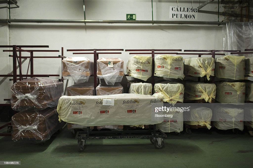 Plastic-wrapped coffins sit on racks inside the storage warehouse of Empresa Mixta de Servicios Funerarios de Madrid SA funeral parlour in Madrid, Spain, on Monday, Dec. 17, 2012. Spain, responding to street protests and reports of suicides linked to foreclosures, introduced rules to help protect families from eviction, increasing the risk of creditor losses and weakening an already fragile banking system. Photographer: Angel Navarrete/Bloomberg via Getty Images