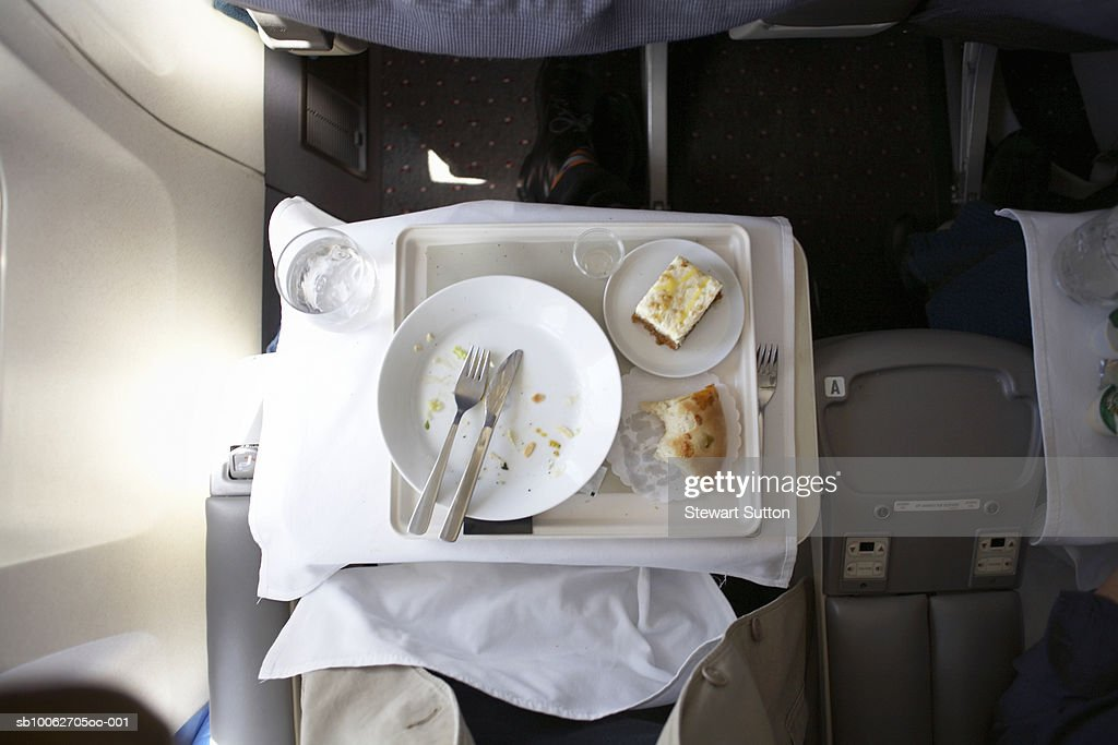Plate and cutlery on tray table in airplane, overhead view : Stock Photo