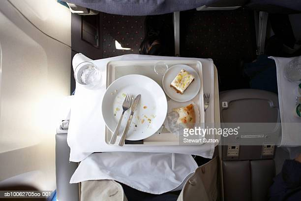 Plate and cutlery on tray table in airplane, overhead view