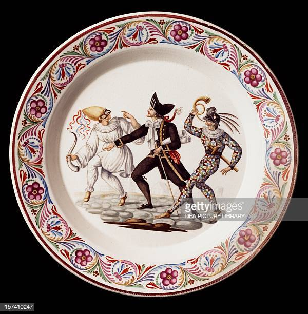 Plate decorated with a scene from Commedia dell'Arte with masks of Pulcinella Arlecchino and Balanzone maiolica Giustiniani manufacture Naples Italy