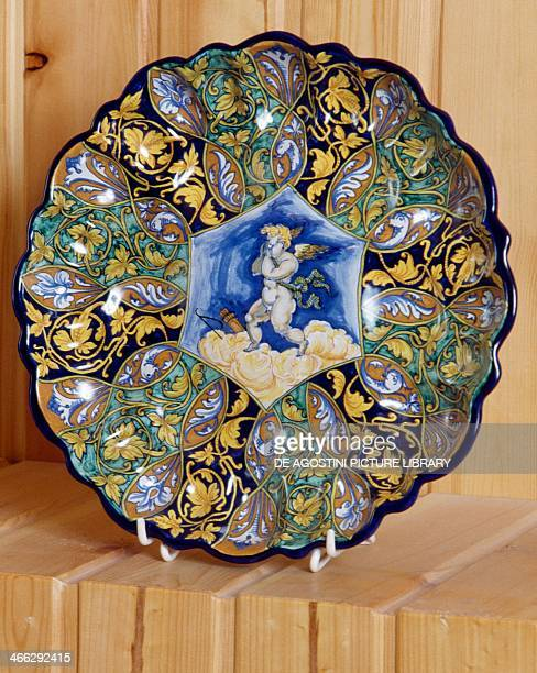 Plate decorated with floral motifs and cherub majolica made in Faenza Italy 20th century