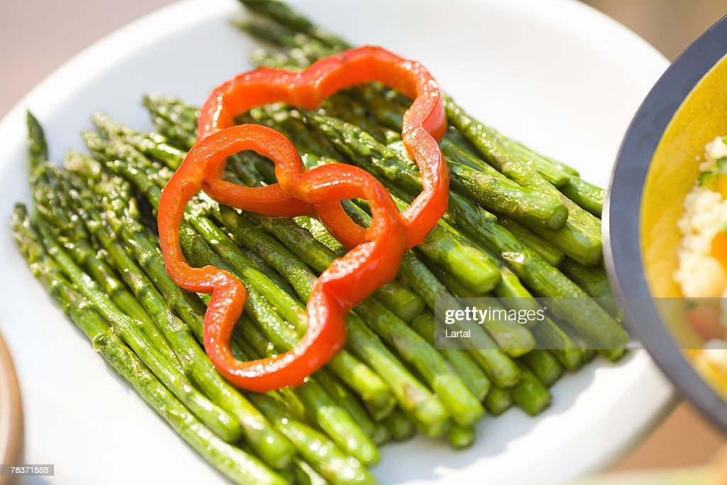 Plate of asparagus with slices of red bell pepper : Stock Photo