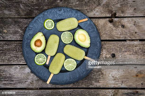 Plate of avocado ice lollies, sliced avocado and slices of lime