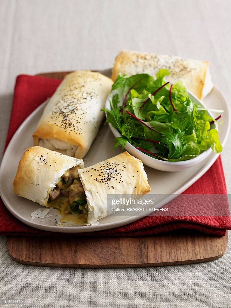Plate of baked pastry rolls with salad : Stock Photo