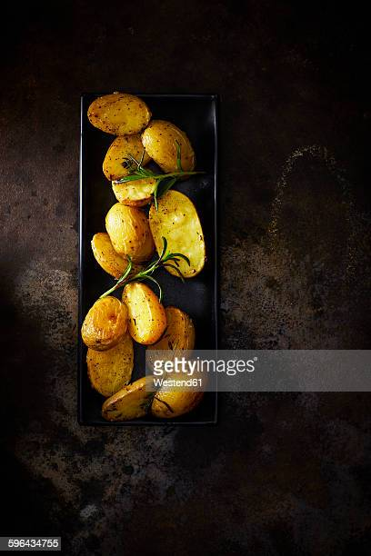 Plate of baked potatoes with rosmary on rusty metal