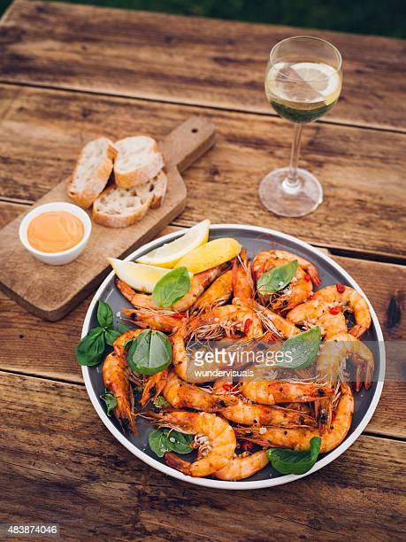 Plate of barbecued prawns with side items and white wine