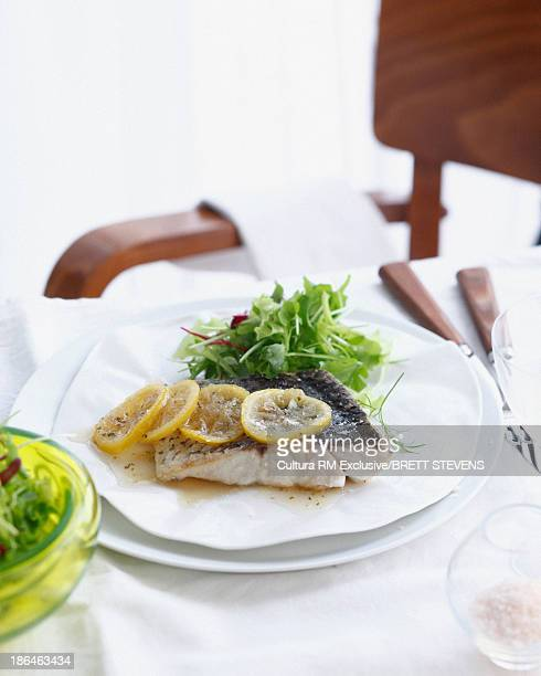 Plate of barramundi fish with salad and lemon slices