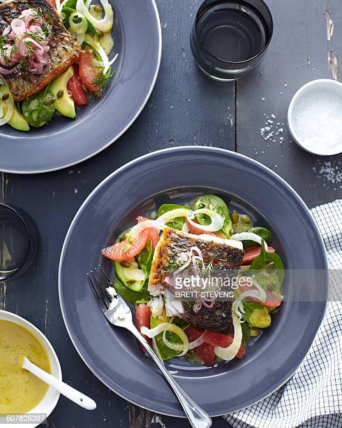 Plate of barramundi fish with vegetables and a herb garnish