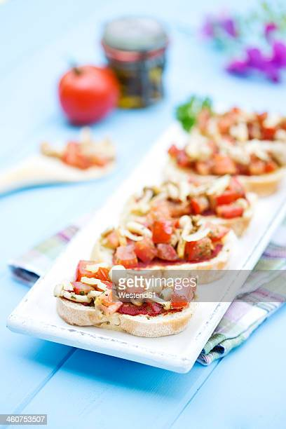 Plate of bruschetta with tomatoes, white shimeji mushrooms, herbs and olive oil on wooden table, close up
