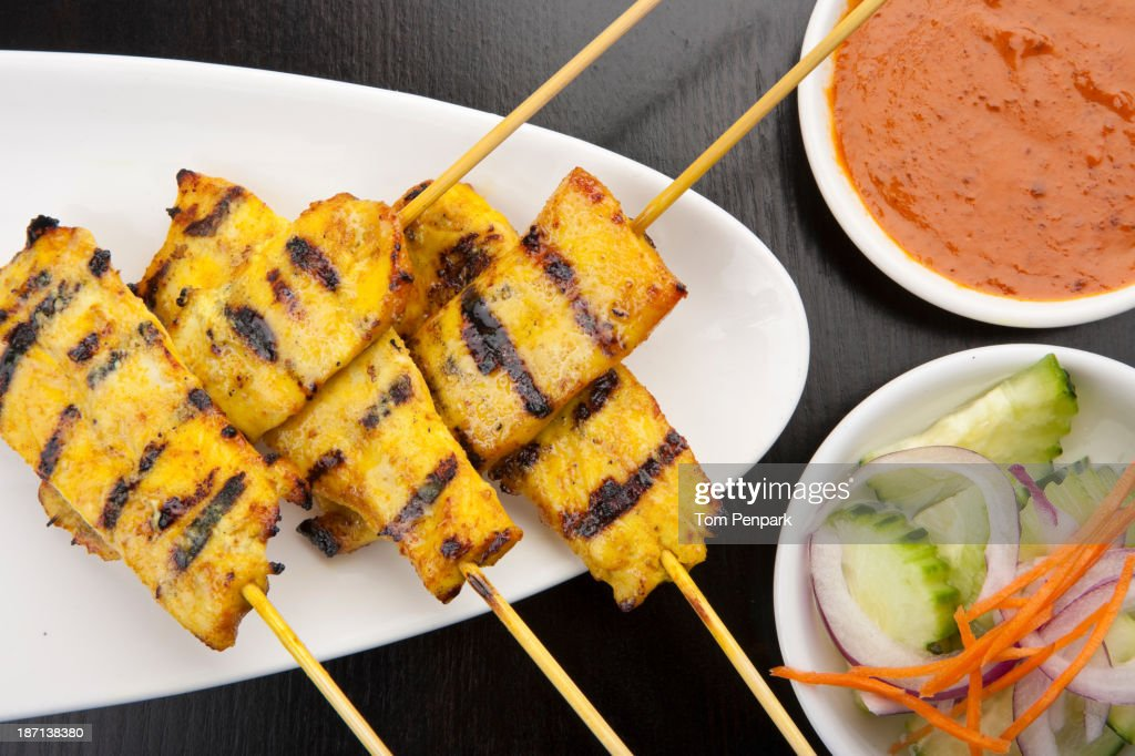 Plate of chicken skewers with salad and peanut sauce : Stock Photo