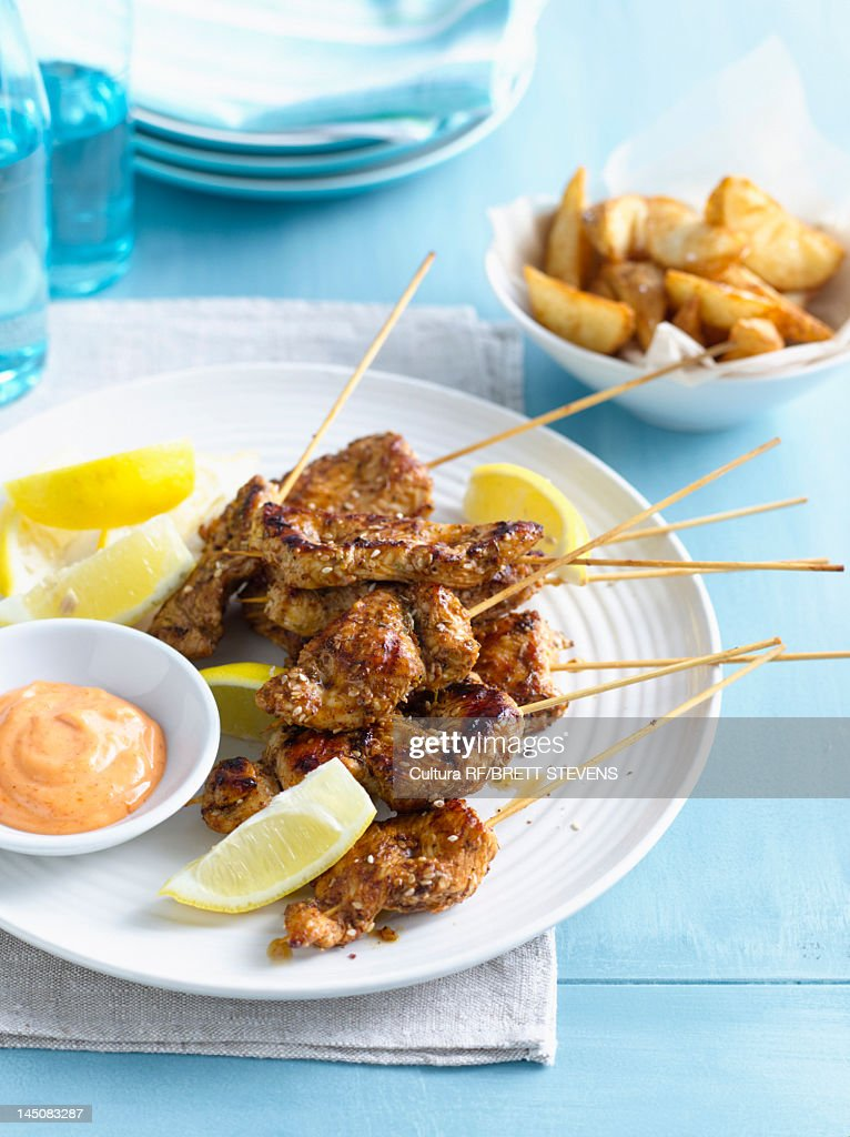 Plate of chicken skewers with sauce : Stock Photo