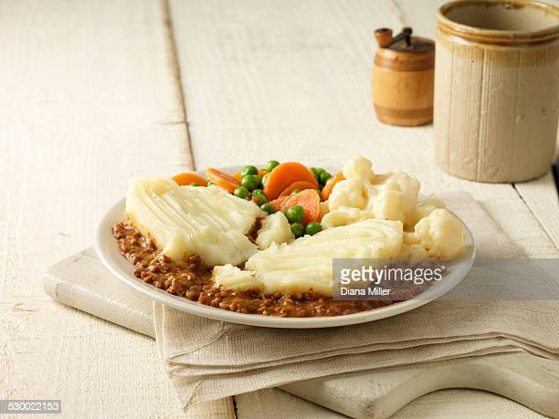 Plate of cottage pie with cauliflower cheese, peas and carrots