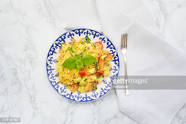 Plate of couscous salad, cloth and fork on white marble