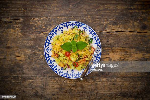 Plate of couscous salad on wood