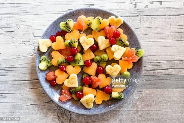 Plate of different heart-shaped fruit pieces
